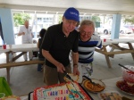 Birthday boy Jaan Kuuskvere cuts the cake under Erkki Taada's watchful eye. KFES piknik, Anna Maria Island, 26 aprill 2015. Foto: Lisa Mets